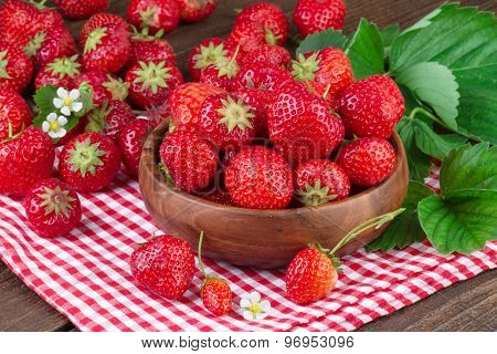 Strawberry in wooden bowl on red checkered tablecloth