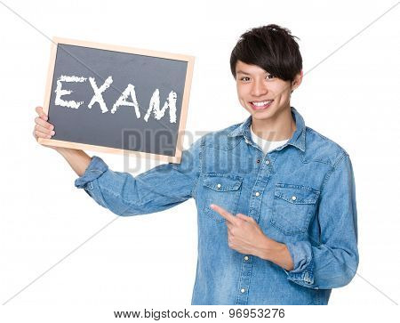 Asian man finger point to chalkboard and showing a word exam