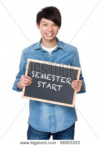 Asian young man with chalkboard showing phrase of semester start