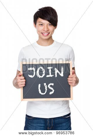 Young man hold with chalkboard showing a phrases of join us