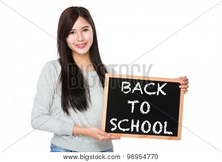 Young woman hold with chalkboard showing phrase of back to school