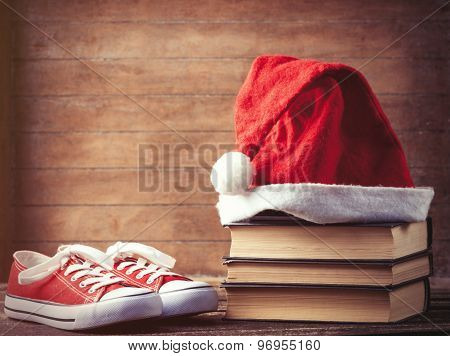 Santas Hat Over Books Near Red Gumshoes