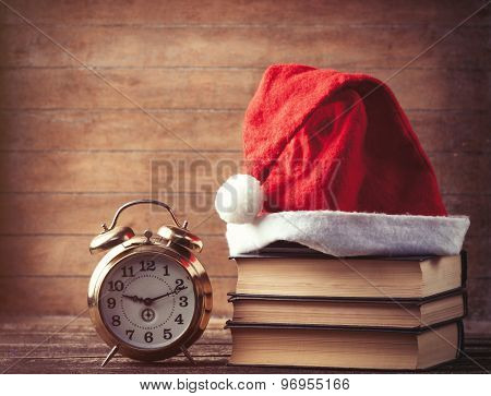 Santas Hat Over Books Near Retro Alarm Clock