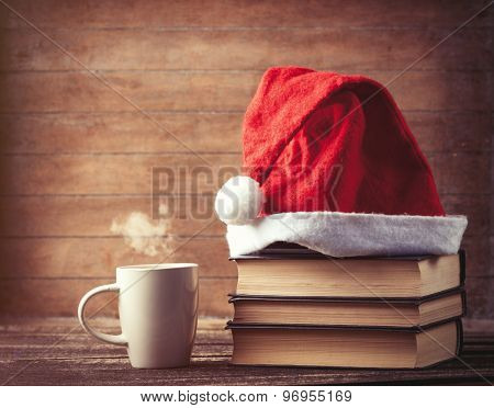 Santas Hat Over Books Near Hot Cup Of Coffee Or Tea