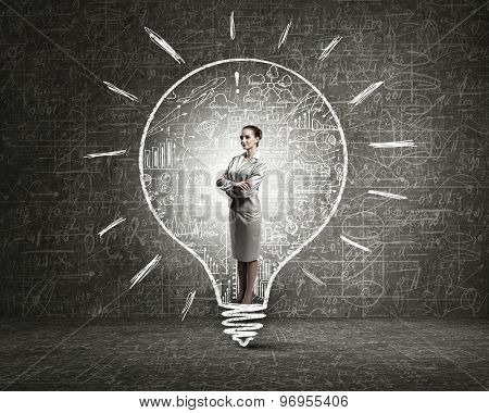 Businesswoman holding luminous idea inside light bulb