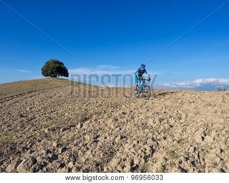 Mountain biker riding through Tuscan landscape