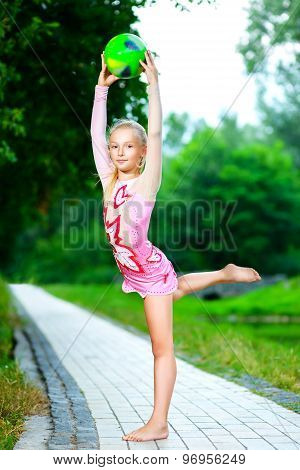 flexible little girl doing gymnastics vertical split with gymnastic Ball
