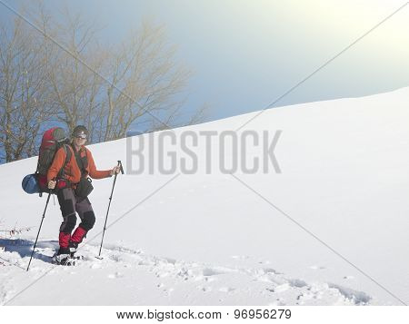 A Man In Snowshoes Is In The Mountains In The Snow.