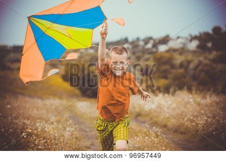 Boy running across the field with kite flying over his head