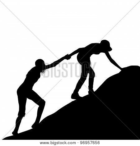 Girl Giving Helping Hand To Her Friend To Climb Up The Last Section Of Mountain