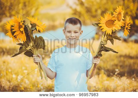 Happy boy with bouquet of sunflowers against summer field