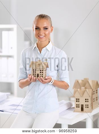Portrait of female architect with blueprints at desk in office.
