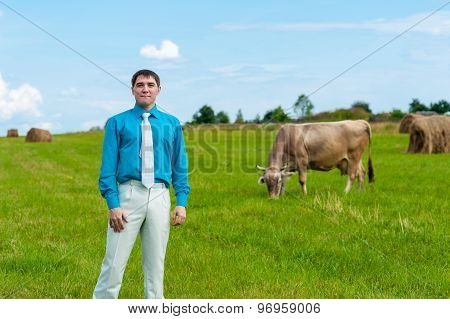 young businessman with agriculture on the background of grass and cow