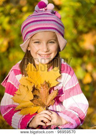little smiling girl against autumn leaves