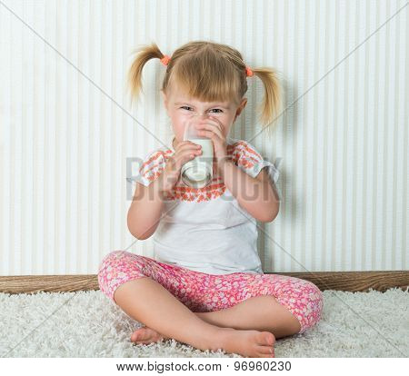 2-year-old girl  drink the milk on the floor in her home