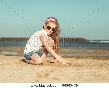 little girl in a hat on a sandy beach