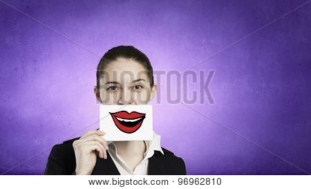 Pretty young girl holding white card with drawn smile