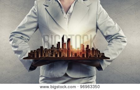 Close up of businesswoman hands presenting building model