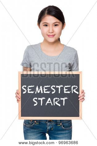 Woman hold with chalkboard and showing phrase semester start