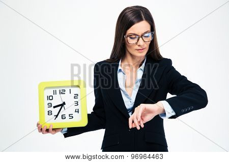 Businesswoman holding wall clock and looking on wristwatch isolated on a white background