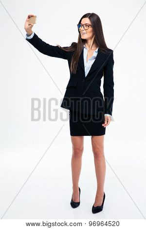 Full length portrait of a smiling businesswoman making selfie photo on smartphone isolated on a white background