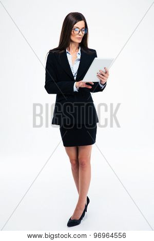 Full length portrait of a businesswoman using tablet computer isolated on a white background