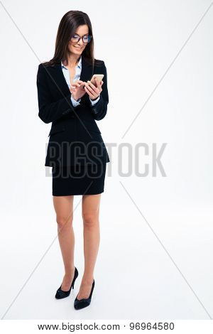Full length portrait of a businesswoman in glasses using smartphone isolated on a white background