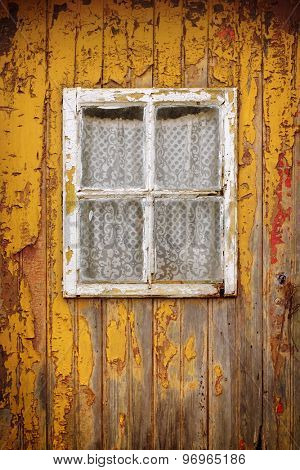 Detail of a weathered yellow wooden door with a small window