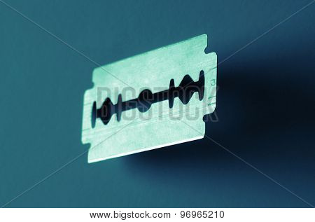 Closeup on an old razor blade over a blue background