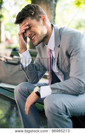 Portrait of depressed businessman sitting on the bench outdoors