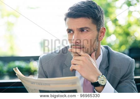 Portrait of a pensive businessman holding newspaper and looking away outdoors