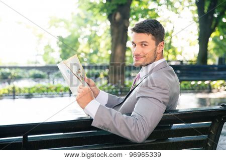Portrait of a happy businessman holding newspaper and looking at camera outdoors