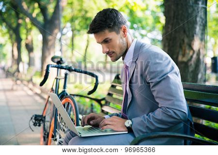 Handsome businessman sitting on the bench outdoors and using laptop