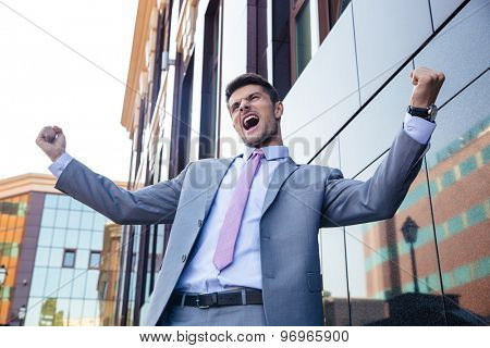 Cheerful businessman celebrating his success outdoors