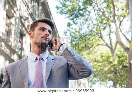 Young pensive businessman talking on the phone outdoors