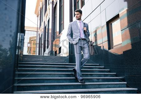 Young handsome businessman walking on stairs outdoors