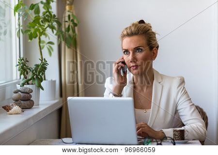 Young business woman talking on phone sitting at a desk with a laptop.
