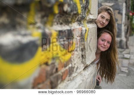 Two cute teen girls look out from behind the corner of a stone house.