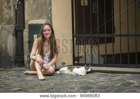 Young cute girl with a cat sitting on a stone pavement.