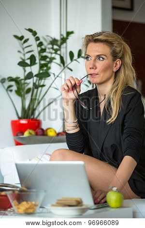 Young beautiful woman sits pensively with a laptop.