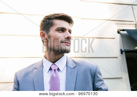 Portrait of a handsome businessman standing outdoors and looking away