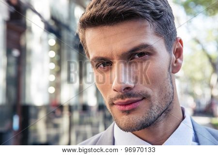 Closeup portrait of a handsome businessman outdoors looking at camera
