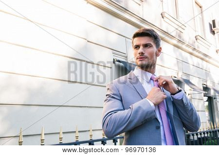 Handsome businessman straightens his tie outdoors