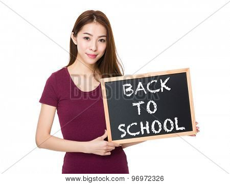 Young woman with blackboard showing phrase of back to school