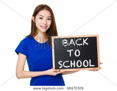 Student hold with wooden chalkboard showing phrase of back to school