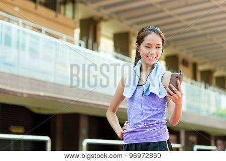 Woman listen to song with mobile phone in sport stadium