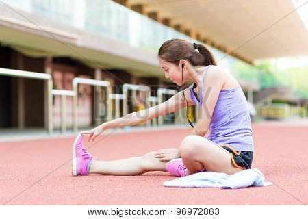 Woman doing stretching and listen to music in sport stadium