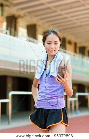 Asain Woman listen to song with cellphone in sport arena