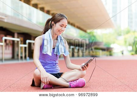Woman listen to song and sitting on sport stadium