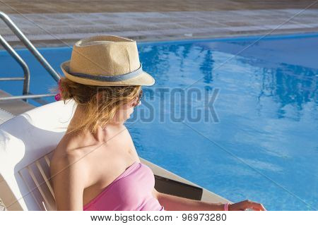 Young Girl Looking At The Swimming Pool From The Sunbed. Girl At Travel Spa Resort Pool. Summer Luxu